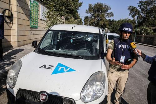 Profissional da imprensa fala à mídia perto do carro, transportando correspondentes do canal nacional de televisão azerbaijani AzTV, após um ataque supostamente realizado pelo exército armênio em 14 de outubro de 2020 no Tártaro, Azerbaijão [Agência Onur Çoban / Anadolu]
