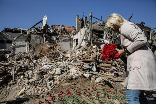 Mulher leva cravos em homenagem a crianças mortas ou feridas por um ataque supostamente executado pelo exército armênio com mísseis de longa distância, na cidade de Ganja, Azerbaijão, 12 de outubro de 2020 [Onur Çoban/Agência Anadolu]
