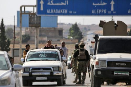 Combatentes sírios apoiados pela Turquia comandam um posto de controle na cidade de Ayn al-Arus, ao sul da cidade fronteiriça de Tal Abyad, em 14 de outubro de 2019 [BAKR ALKASEM / AFP via Getty Images]
