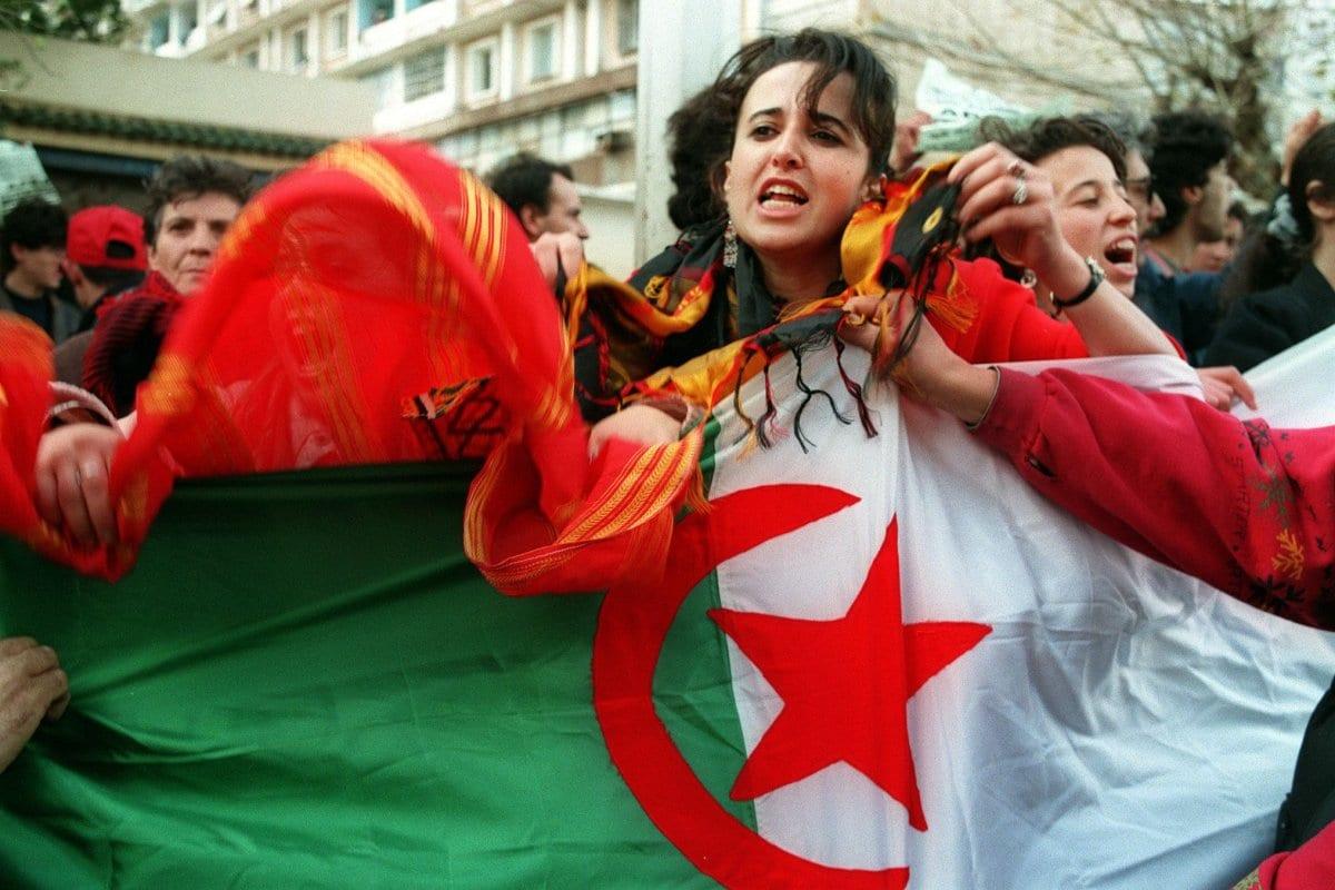 2 jovens berberes agitam bandeiras e gritam slogans [HOCINE ZAOURAR / AFP via Getty Images]