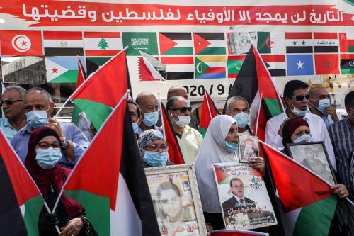 """Manifestantes protestam com bandeiras palestinas diante de uma faixa que mostra as bandeiras dos Estados membros da Liga Árabe com texto em árabe que diz: """"a história glorificará aqueles fiéis à Palestina e sua causa"""", durante um protesto contra os Emirados Árabes Unidos e as decisões do Bahrein de normalizar as relações com Israel, em Nablus, na Cisjordânia ocupada em 15 de setembro de 2020. [Jqfar Ashtiyeh/ AFP via Getty Images]"""