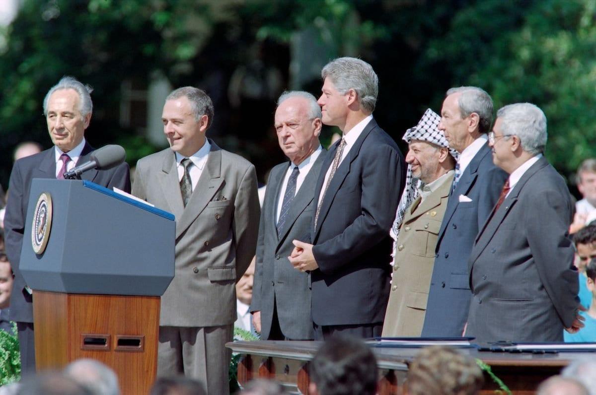 O presidente dos EUA, Bill Clinton (4º dir.) na histórica cerimônia de assinatura dos Acordos de Oslo entre Israel e OLP em 13 de setembro de 1993 na Casa Branca em Washington, DC, ao lado do Ministro das Relações Exteriores de Israel Shimon Peres (esq), das Relações Exteriores da Rússia Ministro Andrei Kozyrev (2º esq.), Primeiro Ministro israelense Yitzhak Rabin (3º E), Presidente da OLP Yasser Arafat (3º dir.), Secretário de Estado dos EUA Warren Christopher (2º dir.) e o diretor político da OLP Mahmoud Abbas (dir). [Luke Frazza/ AFP via Getty Images]