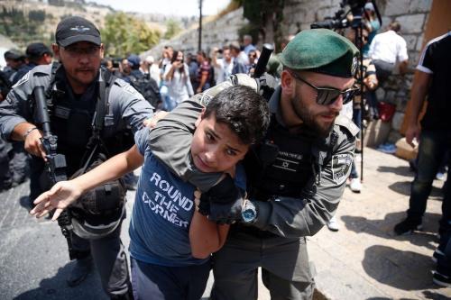 Guardas de fronteira de Israel detêm um menino palestino durante protesto em frente ao chamado Portão do Leão, principal entrada ao complexo de Al-Aqsa, contra medidas de segurança abusivas recém-implementadas, como câmeras e detectores de metal, na Cidade Velha de Jerusalém, 17 de julho de 2017 [Ahmad Gharabli/AFP/Getty Images]