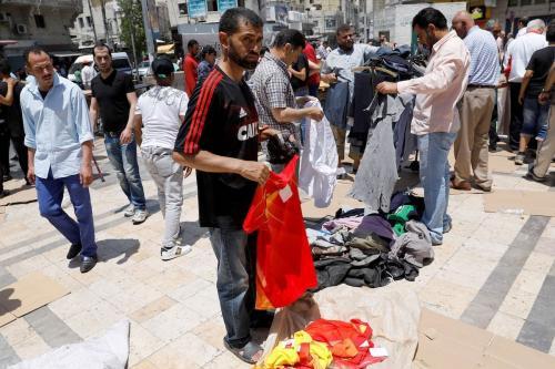 Jordanianos compram roupas de segunda mão em um mercado ao ar livre no centro de Amã em 8 de junho de 2018. [Ahmad Gharabli/ AFP via Getty Images]