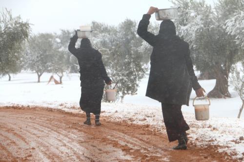 Uma mulher síria caminha com ajuda alimentar em um campo de refugiados na Síria em 21 de dezembro de 2016 [Agência Mamun Ebu Omer/ Agência Anadolu]