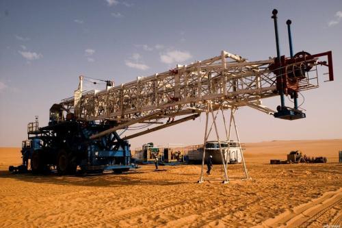 Equipe chinesa daa Repsol quando começava a tarefa de montar uma enorme plataforma de perfuração no meio do deserto, em 5 de junho de 2004, em El- Sharara, Líbia [Benjamin Lowy / Getty Images]