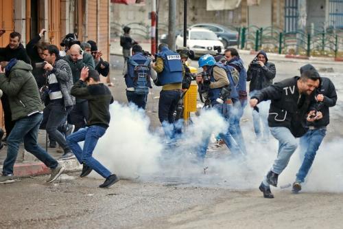 Soldados israelenses lançam granadas de som contra um grupo de pessoas, incluindo jornalistas, perto de um portão que leva à rua principal de Hebron, al-Shuhada, fechada por tropas no início de fevereiro, durante uma manifestação anual em memória do massacre da Mesquita Ibrahimi em 1994, na cidade dividida de Hebron, na Cisjordânia, em 22 de fevereiro de 2019. [Hazem Bader/ AFP via Getty Images]