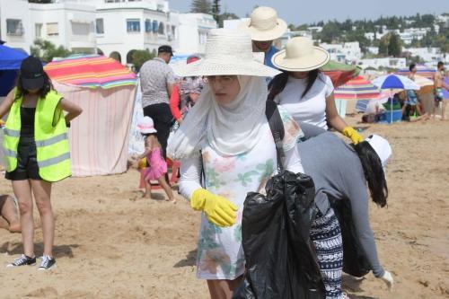 """Voluntários da """"CleanWalker"""" coletam resíduos de uma praia na cidade costeira de Masra em 14 de julho de 2019 perto da capital Túnis [Fethi Belaid/ AFP via Getty Images]"""