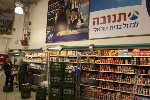 Dois palestinos descarregam mercadorias em um grande supermercado de propriedade de israelenses localizado na junção de Gush Etzion na Cisjordânia palestina em 4 de julho de 2010 [Menagem Kahana/ AFP via Getty Images]