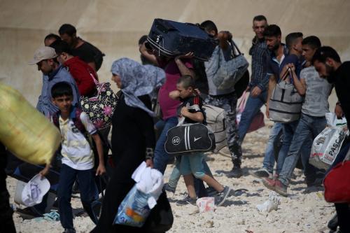 Refugiados sírios com seus pertences atravessam a fronteira em Kilis, Turquia [Ensar Özdemir/Agência Anadolu]