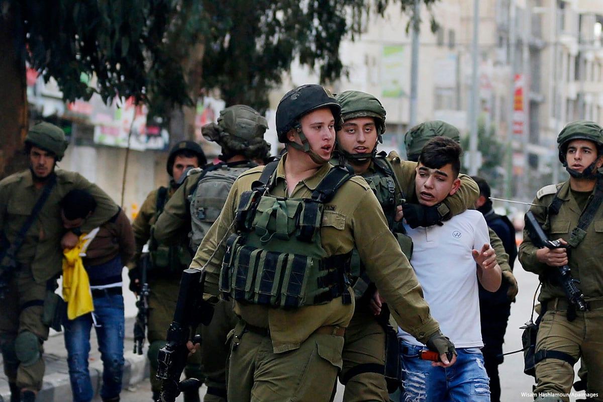 Forças de segurança de Israel detêm um menor de idade palestino, na Cisjordânia ocupada, em 20 de dezembro de 2017 [Wisam Hashlamoun/Apaimages]