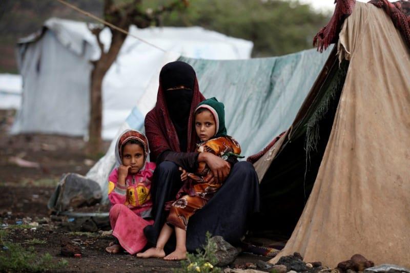 Uma mãe e suas filhas sentam-se em frente a uma tenda improvisada em um campo para deslocados internos no Iêmen, perto da capital Sanaa, em 15 de agosto de 2016 [Khaled Abdullah/Reuters]