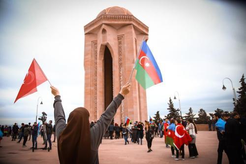 Cidadãos azeris visitam a Praça dos Mártires, cemitério e memorial dedicado aos combatentes mortos por tropas soviéticas em 1990, para celebrar o acordo de cessar-fogo sobre os confrontos recentes em Nagorno-Karabakh, em Baku, Azerbaijão, 10 de novembro de 2020 [Resul Rehimov/Agência Anadolu]