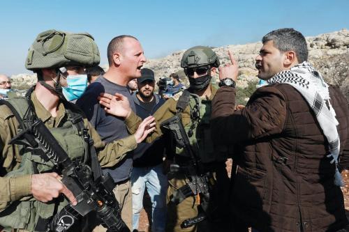 Soldados israelenses intervêm quando palestionos reagem á tentativa de colonos de confisco de suas terras agrícolas d na região de al-Ras em Selfit, Cisjordânia em 30 de novembro de 2020. [Issam Rimawi/Agência Anadolu]