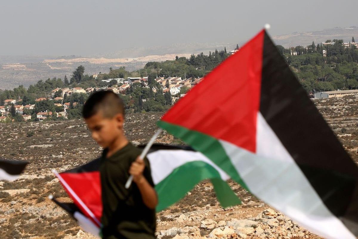 Um menino palestino carrega uma bandeira nacional em protesta contra a proibição israelense de construção de um campo de jogos para deficientes na cidade ocupada de Salfit, na Cisjordânia, perto do assentamento ilegal Ariel, de Israel, em 28 de outubro de 2020. [Jaafar Ashtiyeh via Getty Images]