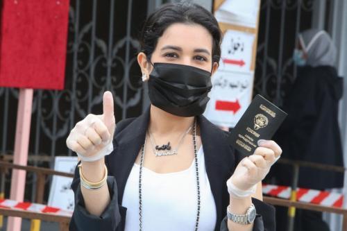 Mulher kuwaitiana, vestindo máscara e luvas devido ao covid-19, chega a um posto eleitoral para registrar seu voto ao parlamento nacional, na Cidade do Kuwait, 5 de dezembro de 2020 [Yasser al-Zayyat/AFP/Getty Images]