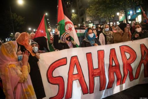 Mulheres com bandeiras do Saara e vestidas de Malahfas participam de manifestação para exigir o fim da ocupação marroquina do Saara Ocidental, em apoio à Frente Polisário e para exigir soluções do governo espanhol em 16 de novembro de 2020 em San Sebastian, Espanha. [Gari Garaialde / Getty Images]