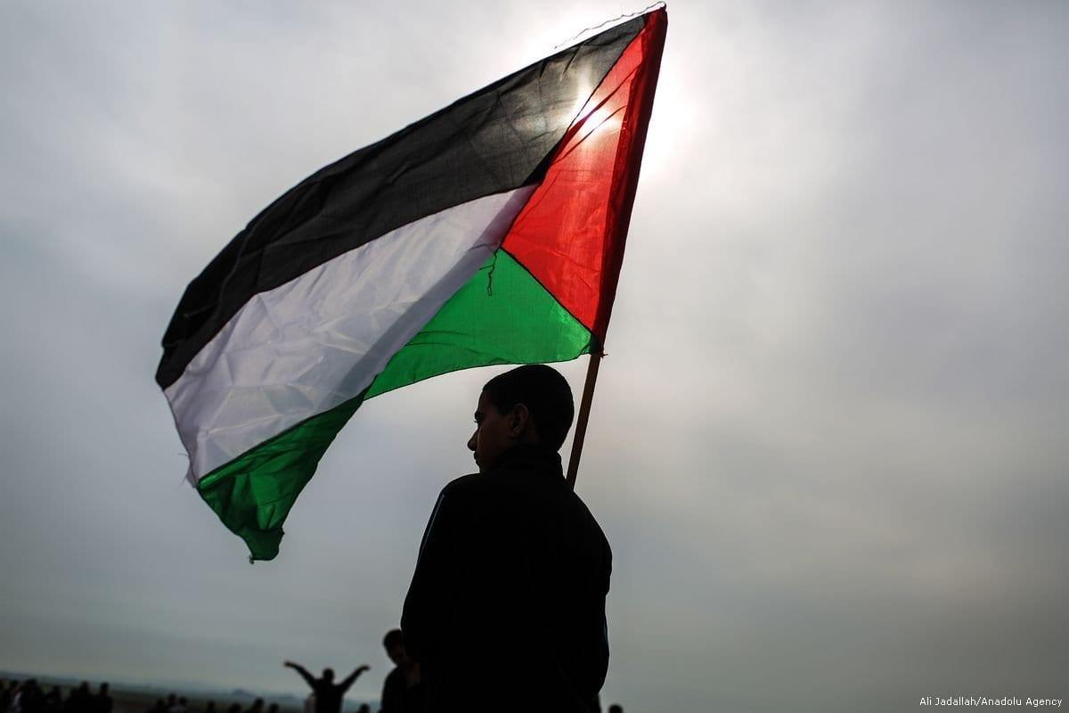 Um menino palestino segura uma bandeira palestina, 29 de dezembro de 2017 [Ali Jadallah / Agência Anadolu