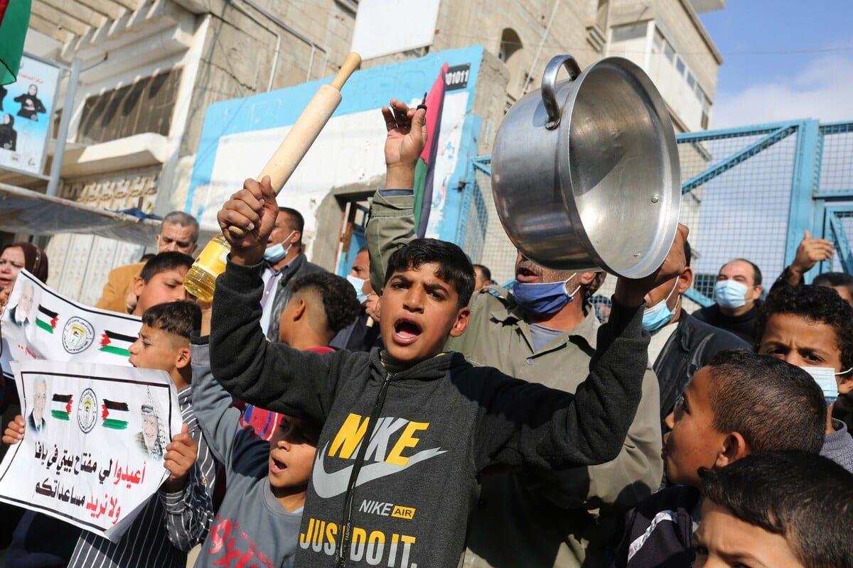Palestinos reunidos em frente à Agência das Nações Unidas de Assistência aos Refugiados Palestinos (UNRWA) fazem uma manifestação contra a redução de serviços, em Khan Yunis, Gaza, em 23 de dezembro de 2020. [Ashraf Amra/Agência Anadolu]