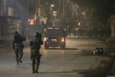 Manifestantes tunisianos entram em confronto com policiais enquanto violam o toque de recolher imposto para conter a pandemia do coronavírus, durante um protesto contra as condições de vida e o desemprego no distrito de At-Tadaman na capital Túnis, Tunísia, em 15 de janeiro de 2021. [Yassine Gaidi/Agência Anadolu]