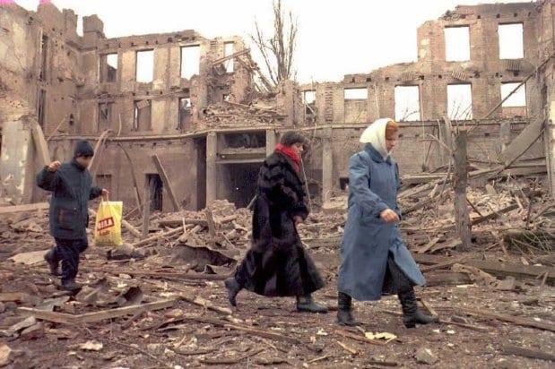 Civis chechenos caminham em meio às ruínas de Grozny, Chechênia, 1° de janeiro de 1995 [Oleg Nikishin/AFP/Getty Images]