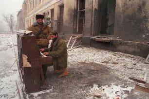 Combatente separatista da Chechênia toca piano entre as ruínas de Grozny, 27 de dezembro de 1994 [Oleg Nikishin/AFP/Getty Images]