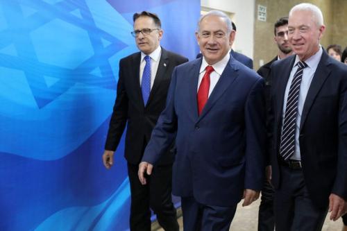 O primeiro-ministro israelense Benjamin Netanyahu (centro) chega à reunião de gabinete semanal em seu escritório em Jerusalém, em 7 de julho de 2019, acompanhado pelo secretário de gabinete Tzachi Braverman (esq.) e pelo ministro da Imigração e Absorção Yoav Galant (dir.). [Abir Sultan/AFP via Getty Images]
