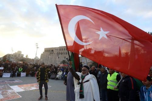 Manifestantes líbios com uma enorme bandeira turca participam de um ato contra o general renegado Khalifa Haftar, em apoio ao Governo de União Nacional, reconhecido pela ONU, na Praça dos Mártires, em Trípoli, Líbia, 10 de janeiro de 2020 [Mahmud Turkia/AFP/Getty Images]