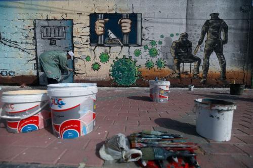 Um artista palestino pinta um mural em uma demonstração de apoio aos prisioneiros palestinos mantidos em prisões israelenses em meio à pandemia de covid-19, na Cidade de Gaza, em 20 de abril de 2020. [Mohammed Abed/AFP via Getty Images]