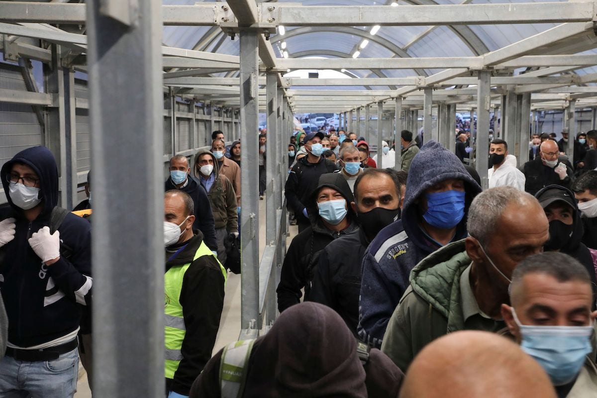 Trabalhadores palestinos aguardam em fila para atravessar um posto de controle militar israelense na cidade de Hebron (Al-Khalil), Cisjordânia ocupada, em 3 de maio de 2020 [Hazem Bader/AFP/Getty Images]