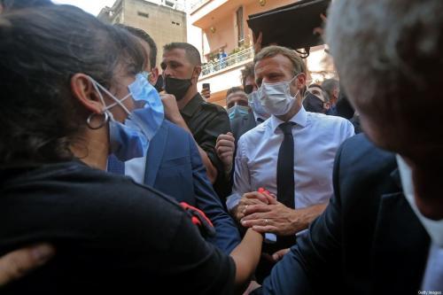 Presidente da França Emmanuel Macron conversa com jovem libanesa durante visita ao bairro de Gemmayzeh, bastante danificado pela enorme explosão no porto de Beirute, capital do Líbano, 6 de agosto de 2020 [AFP/Getty Images]