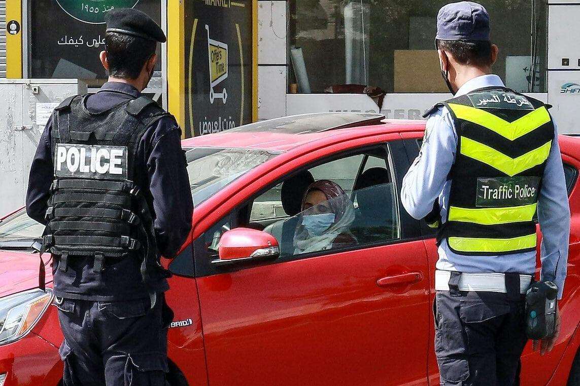 Policiais jordanianos param um veículo e verificam os documentos de identificação de seu motorista em um posto de controle durante um bloqueio de coronavírus na capital Amã, em 9 de outubro de 2020. [Khalil Mazeaawi/AFP via Getty Images]