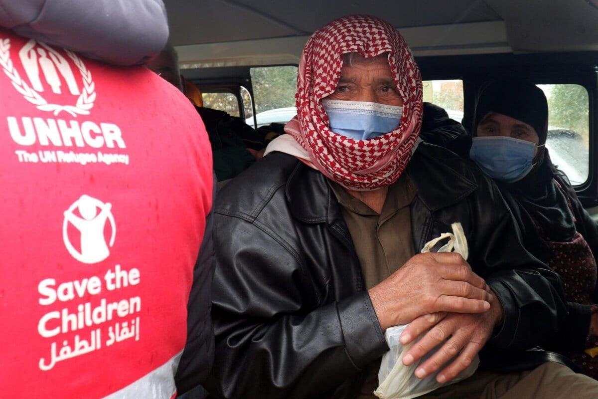 Refugiado sírio com máscara e baseado na Jordânia chega a bordo de um ônibus para receber uma dose de vacinação contra a covid-19 em um centro médico governamental em Mafraq, no norte da Jordânia, em 18 de janeiro de 2021. [Khalil Mazraawi/AFP via Getty Images]