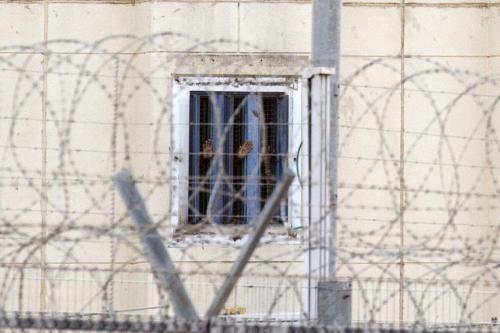 Prisioneiros gesticulam de suas celas, na prisão de segurança máxima de HaSharon (Rimonim), a cerca de 40 km nordeste de Tel Aviv, em 23 de fevereiro de 2014 [Jack Guez/AFP/Getty Images]