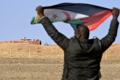 Homem saarauí exibe uma bandeira da Frente Polisário perto do muro que separa o Saara Ocidental do Marrocos, em 3 de fevereiro de 2017 [Stringer/AFP/Getty Images]