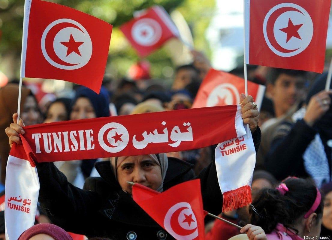 Uma mulher segura a bandeira nacional tunisiana durante um protesto em 14 de Janeiro de 2016 [FETHI BELAID/AFP/Getty Images]