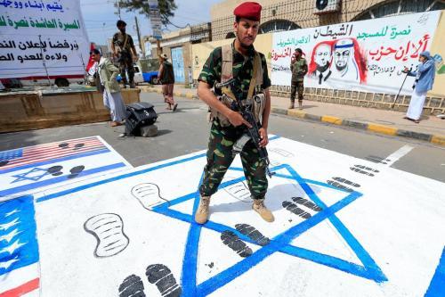 Um lutador leal aos rebeldes Huthi do Iêmen pisa bandeiras dos Estados Unidos e de Israel pintadas no chão durante um comício na capital Sanaa, em 22 de agosto de 2020, para protestar contra o acordo mediado pelos Estados Unidos para normalizar as relações entre Emirados e Israel. [Mohammed Huwais/AFP via Getty Images]