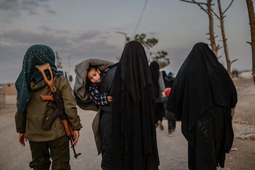 Mulheres sírias caminham sob escolta de uma combatente das Forças Democráticas Sírias (FDS) no campo de refugiados de Al-Hol, na Síria, em 17 de fevereiro de 2019 [Bulent Kilic/AFP/Getty Images]