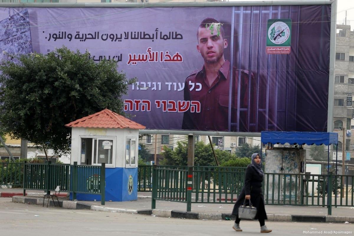 Outdoor na junção de Al-Saraya retrata o soldado israelense Oron Shaul atrás das grades, na Faixa de Gaza [Mohammed Asad/Apaimages]