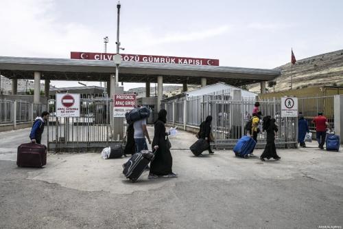 Os sírios passam pelo portão da fronteira de Cilvegozu para chegar às suas cidades natais antes de Eid al-fitr, em Reyhanli, Hatay, em 31 de maio de 2019. [Cem Genco/Anadolu Agency]