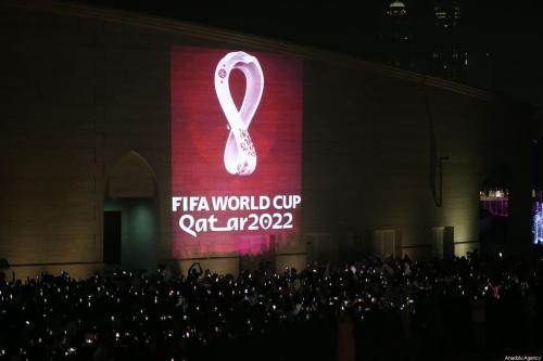 Centenas de pessoas tiram fotos enquanto o logotipo oficial da 'Copa do Mundo FIFA Qatar 2022' é refletido em uma parede em Doha, Catar, em 3 de setembro de 2019. [Mohammed Dabbous/Agência Anadolu]