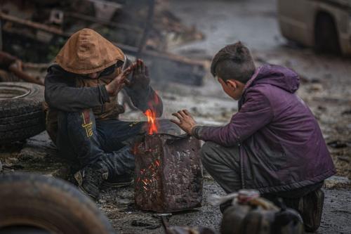 Crianças sírias tentam se aquecer durante o inverno de Idlib, em 30 de janeiro de 2021 [Muhammad Said/Agência Anadolu]