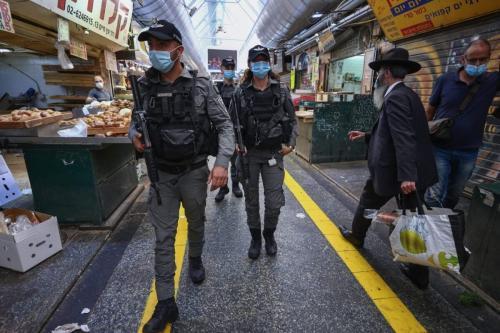 Policiais da fronteira israelense patrulham o principal mercado de Jerusalém durante o fechamento como uma série de medidas para fortalecer o bloqueio da covid-19. [Emmanuel Dunand/AFP via Getty Images]