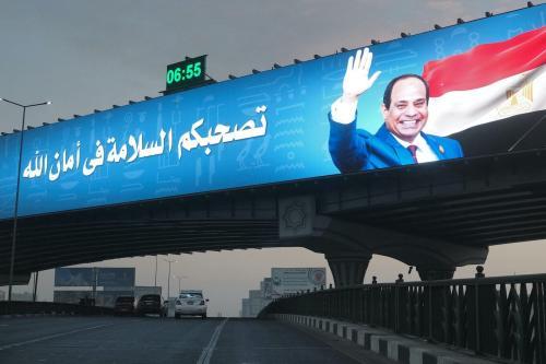 Outdoor eletrônico gigante no topo de uma ponte recentemente construída exibe o presidente Abdel Fattah al-Sisi ao lado de uma mensagem desejando viagens seguras aos motoristas que passam no distrito de Nasr City, capital do Egito, Cairo, em 15 de janeiro de 2021. [Amir Makar / AFP via Getty Images]