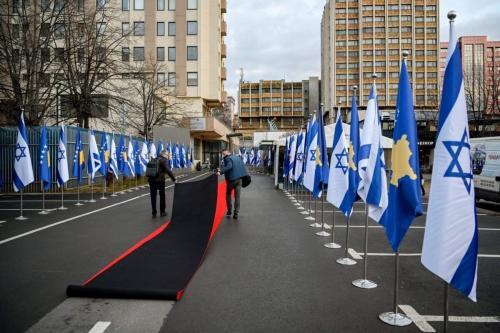 Trabalhadores estendem o tapete vermelho ao lado das bandeiras de Kosovo e Israel exibidas durante uma cerimônia na sede do Ministério das Relações Exteriores em Pristina em 1 de fevereiro de 2021 [Armed Nimani/ AFP via Getty Images]