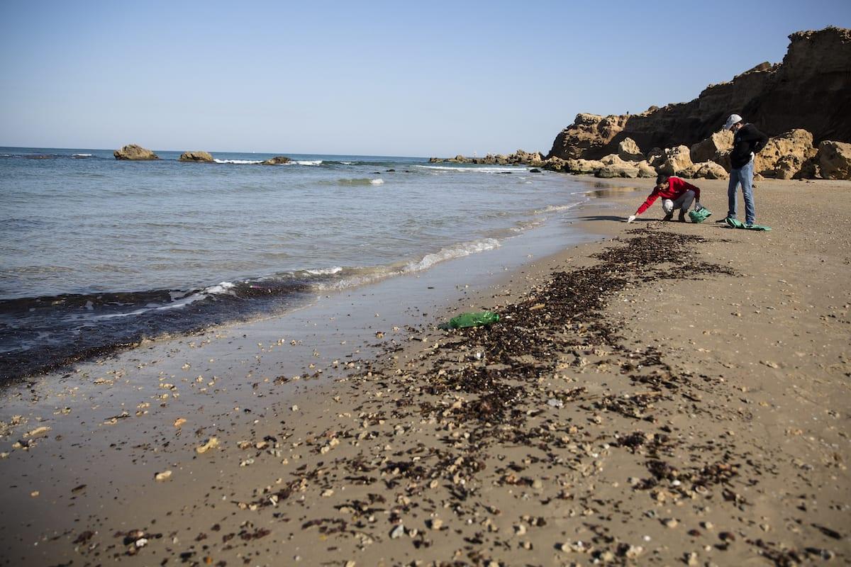 Homens recolhem alcatrão da areia como parte do esforço de limpeza da praia depois que o material cobriu a costa de Israel em 22 de fevereiro de 2021 em Hadera, Israel. [Amir Levy ]