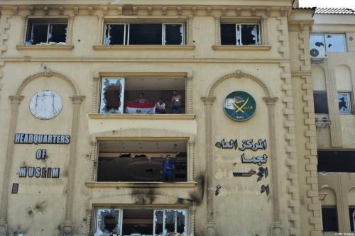 Manifestantes egípcios estão no quartel-general queimado da Irmandade Muçulmana no distrito de Moqattam, no Cairo, em 1 de julho de 2013. [Khaled Desouki/AFP via Getty Images]