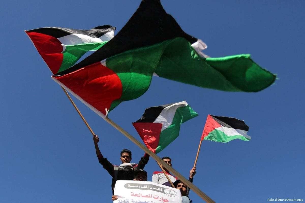 Palestinos exibem a bandeira nacional durante ato em apoio à reconciliação, na Cidade de Gaza, em 3 de dezembro de 2017 [Ashraf Amra/Apaimages]