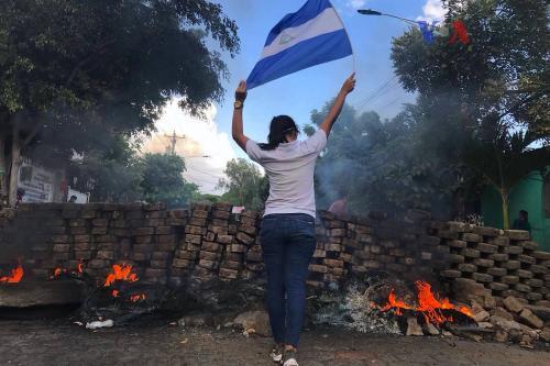 Uma mulher segurando a Bandeira da Nicarágua perto duma barricada em chamas. [Foto Wikipedia]