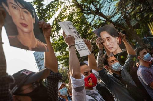 Manifestantes seguram retratos de Aung San Suu Kyi durante um protesto em frente à Embaixada de Mianmar em Bangkok , Tailândia em 1 de fevereiro de 2021. [Guillaume Payen/ Agência Anadolu]